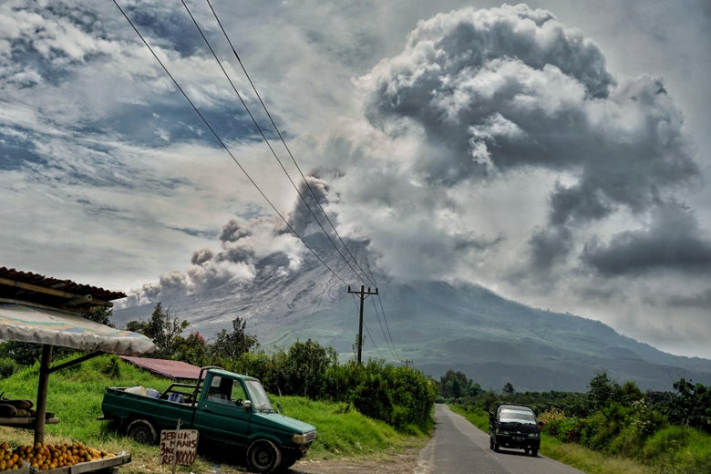 A volcano erupts and spews ash over a village
