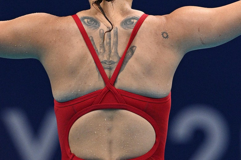 The back of a female diver in her competitive bathing suit, stretching her arms out to the sides, a tattoo visible between her shoulder blades of two eyes, below which are inked the back of a hand and a mouth inside the base of that hand