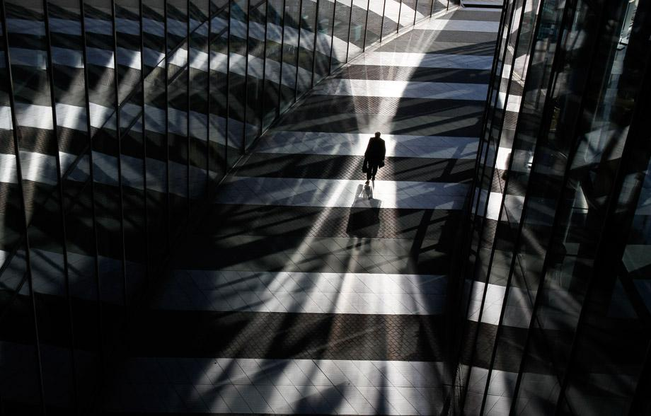 A man walks between glass facades of the Bonn Post Tower, the headquarters of German postal and logistics group Deutsche Post DHL in Bonn March 5, 2013.
