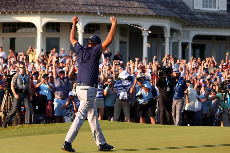 Mickelson with his arms raised in triumph on the green, crowd going wild behind him.