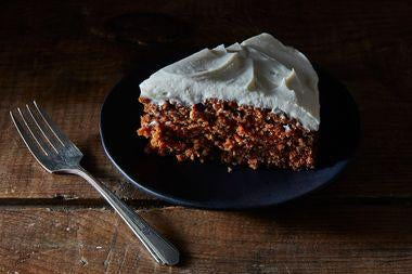A crumbly brown cake dotted with orange and topped with a thick white frosting.