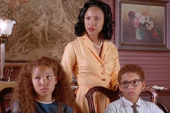 Young Journee and Jake Smollett sit at a table with Lynn Whitfield standing behind them.