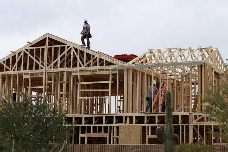 A worker climbs on the roof of a home under construction.