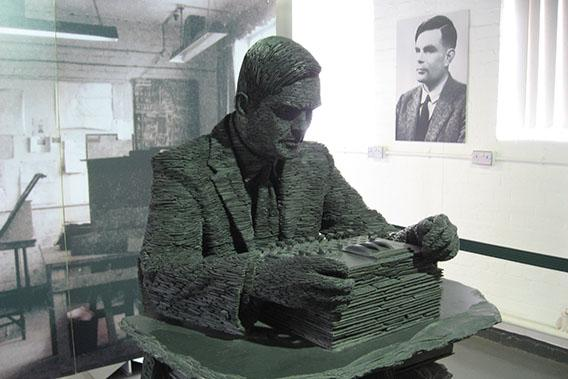 A statue of Alan Turing with his portrait in the background.