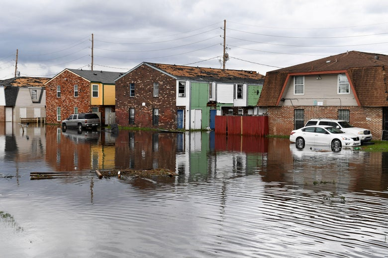 Several homes in the background of a flooded road.