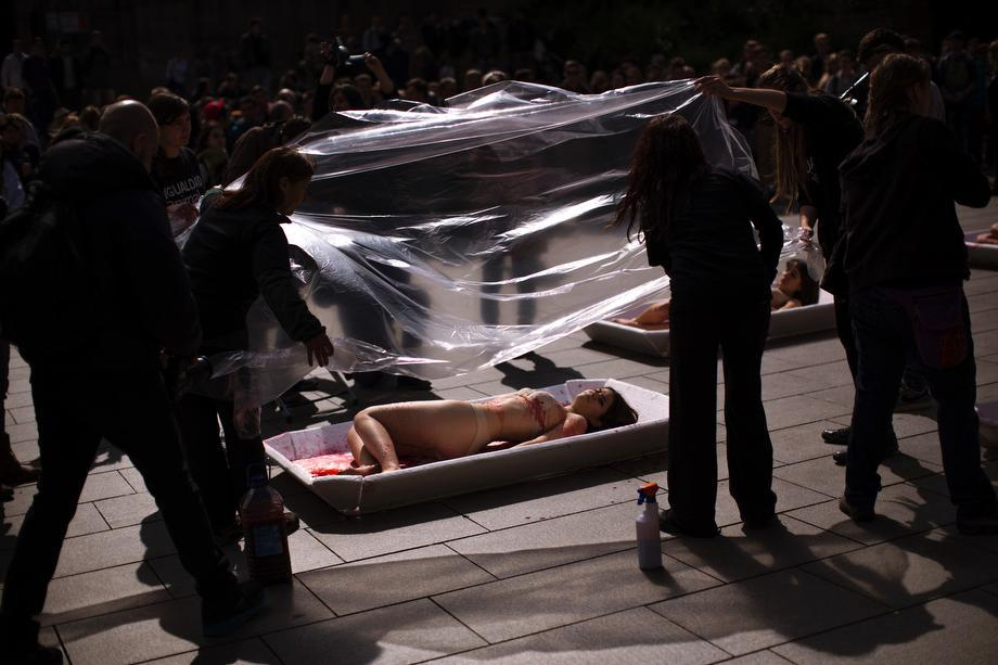 """Animal rights activist from the group 'Animal Equality' are covered with plastic sheets to represent meat packaging as they stage a protest during """"Day Without Meat"""" event in Barcelona, Spain on March 20, 2013."""