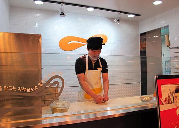 An employee kneads dough at Mr. Pizza.