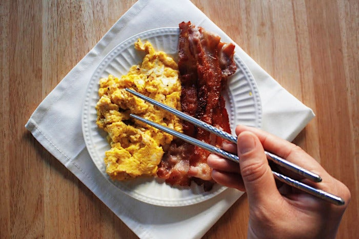 Chopsticks with a plate of eggs and bacon
