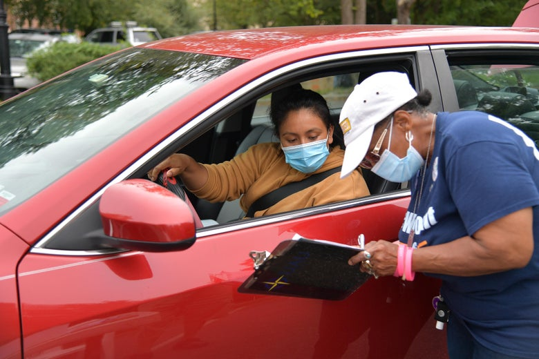 A woman in a face mask fills out a form with another woman in a car