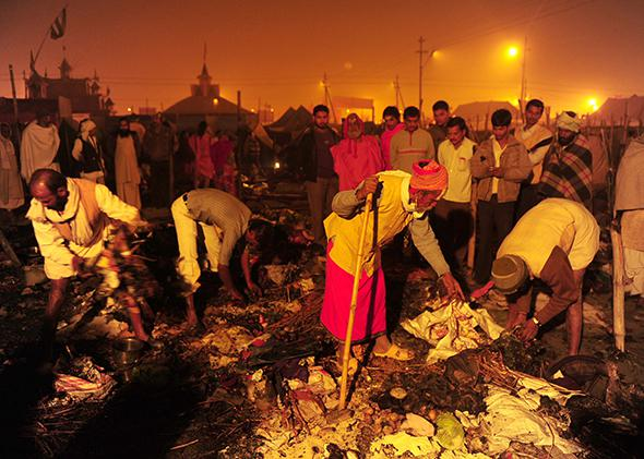 Hindu holy men search for salvageable belongings after a fire destroyed their tents at the Kumbh Mela in Allahabad, India, on Jan. 25, 2013. Nineteen people were injured in the fire, a local report said citing officials.