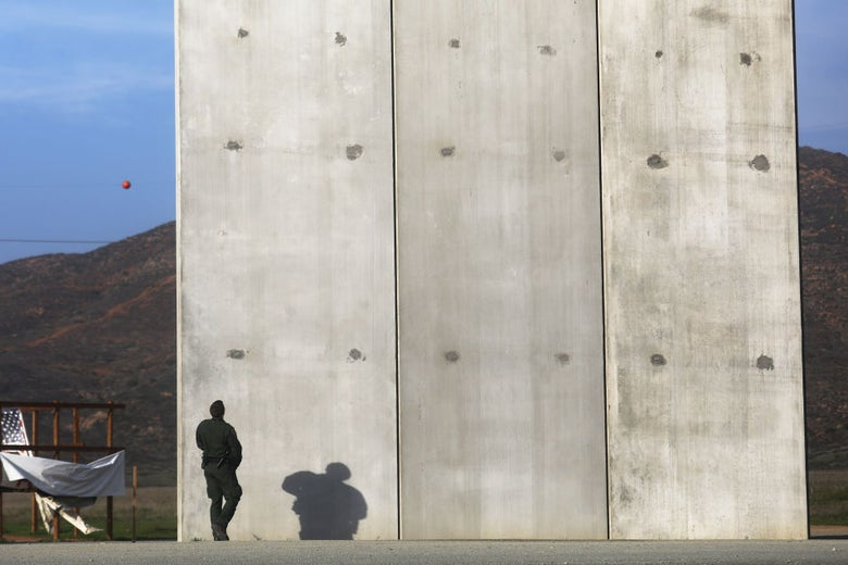A man in a green uniform stands in front of a concrete wall that appears to be about 30 feet high.