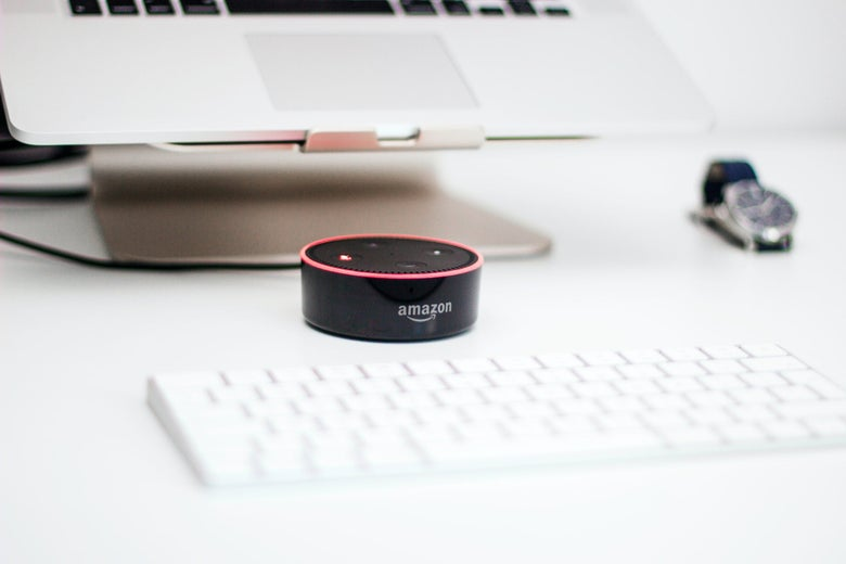 An Amazon Echo sits on a white tabletop between a white keyboard and a laptop on a stand.