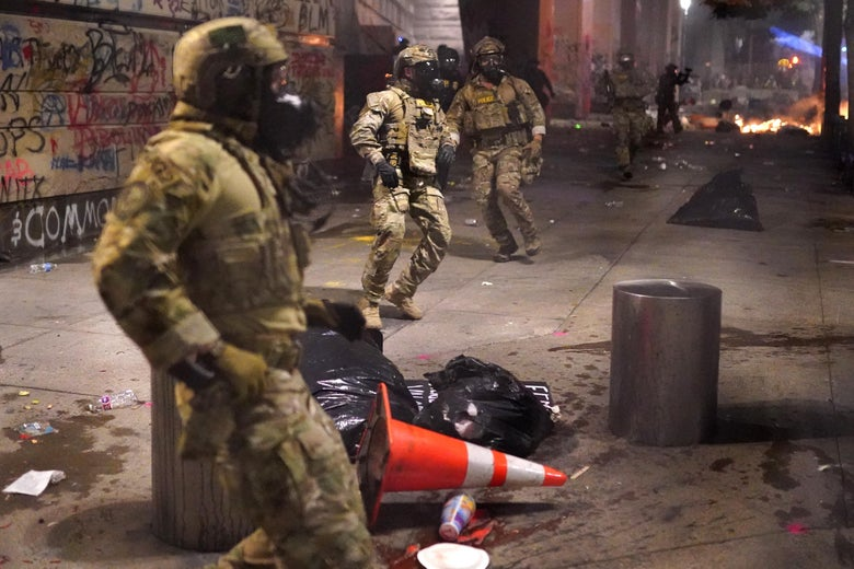 Federal officers in gas masks and camo gear surrounded by trash and graffiti.