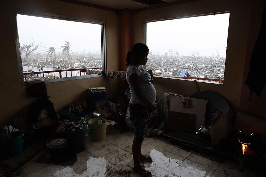 A pregnant woman cooks a meal inside a building overlooking destroyed houses after Super Typhoon Haiyan battered Tacloban city in central Philippines November 10, 2013.