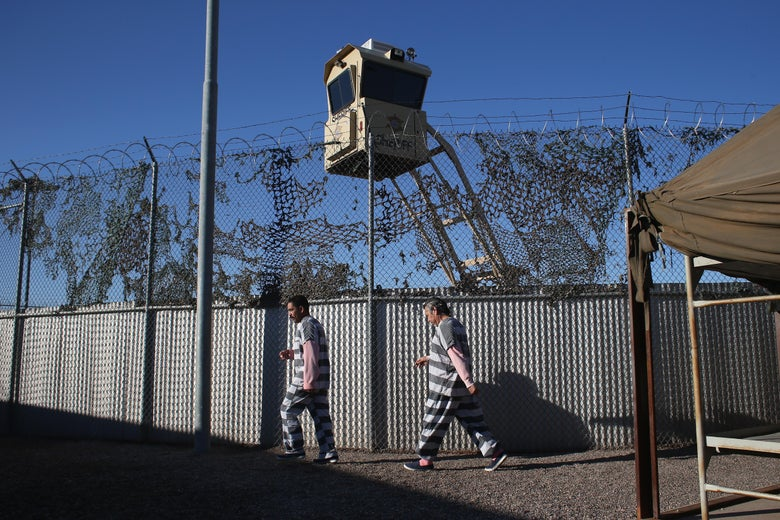 Inmates in striped uniforms walk outside a jail in Arizona