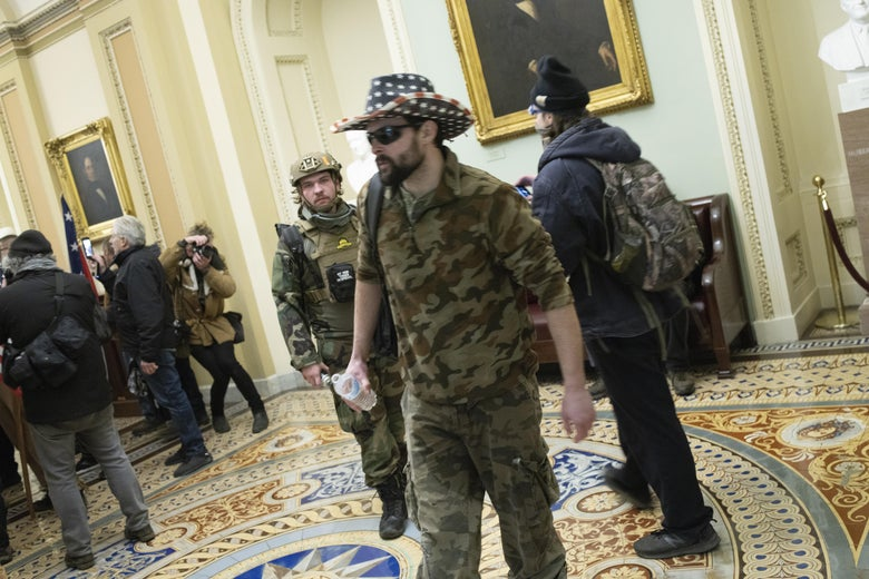 Men in army camo parade around the Capitol during the riot.
