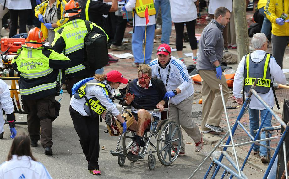 A person who was injured in an explosion near the finish line of the 117th Boston Marathon is taken away from the scene in a wheelchair.