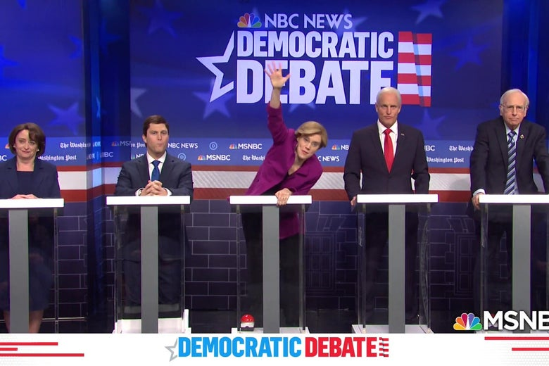 Rachel Dratch, Colin Jost, Kate McKinnon, Woody Harrelson, and Larry David stand behind debate podiums playing Democratic contenders.