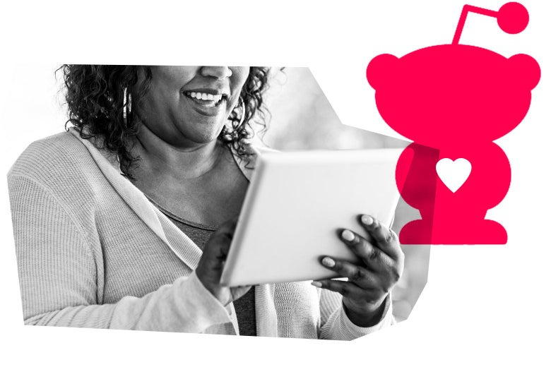 A Black woman smiles while looking at her tablet. A Reddit logo is in the background.