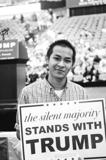 17-year-old Joseph Le poses with his sign before the rally, in D