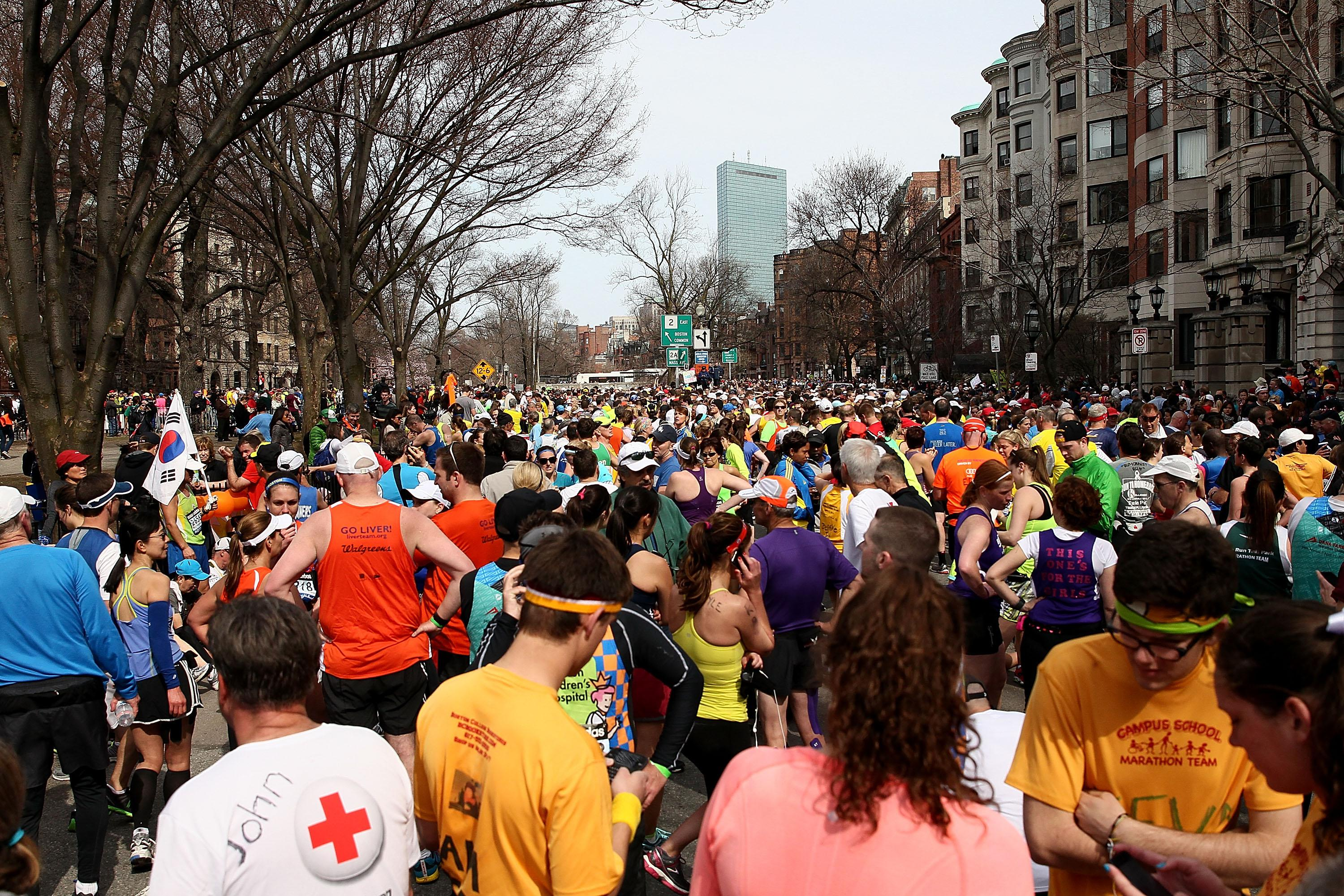 Runners gather near Kenmore Square after two bombs exploded during the 117th Boston Marathon.
