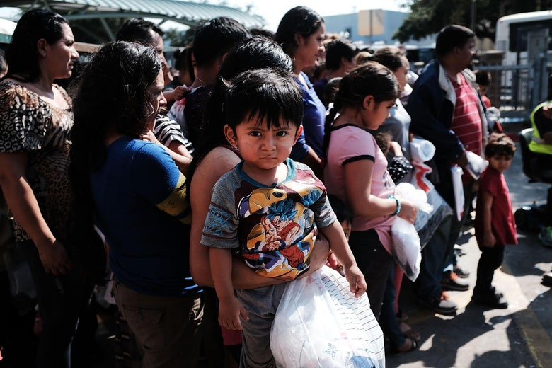 A small child at the center of a group of immigrants at the border in Texas.