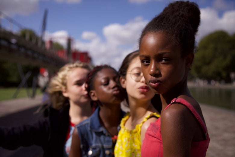Four young women face the camera, their lips pursed in a kiss.