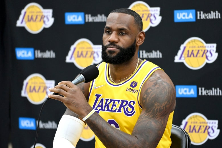 LeBron seated holding the mic in front of him, looking serious