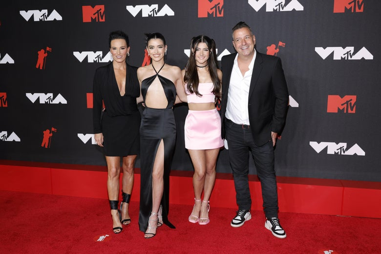 Four people (three women and one man) stand on a red carpet in front of a black banner that says MTV VMAs on it in red and white letters. The two women on the left wear black dresses and heels; the third woman, in the middle, wears a pink two-piece dress and pink heels. The man, to the far right, wears a black suit, white shirt, and black-and-white sneakers. They smile at the camera.