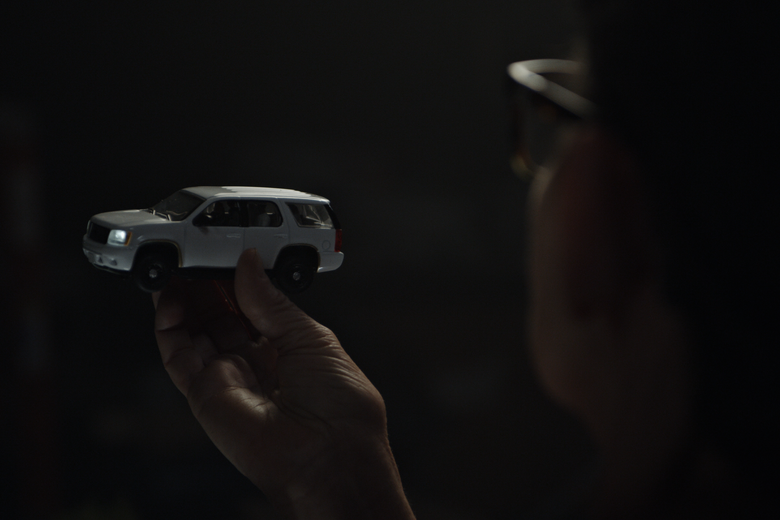 A hand holds up a miniature model of a white SUV