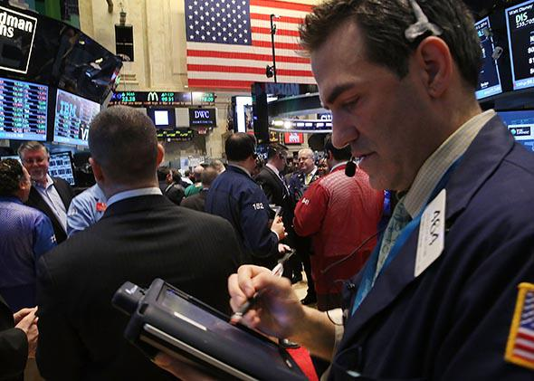 Traders work on the floor of the New York Stock Exchange after the ringing the Opening Bell on April 1, 2014 in New York City.