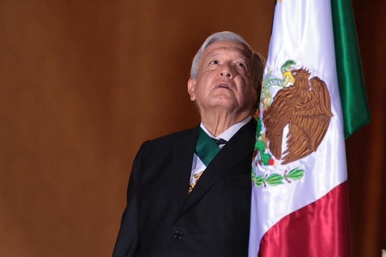 Andrés Manuel López Obrador gazes at a Mexican flag.