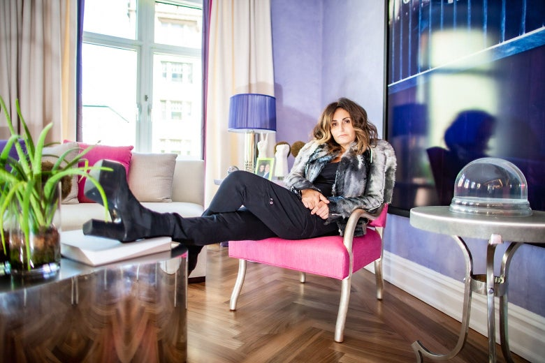 A woman sits in a chair with her foot up on a coffee table. She wears black stacked-heel boots, black pants, and a gray jacket.