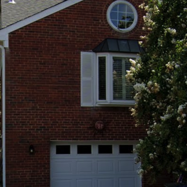 The same house, without the address numbers, but with a yellow sun hanging above the garage door.