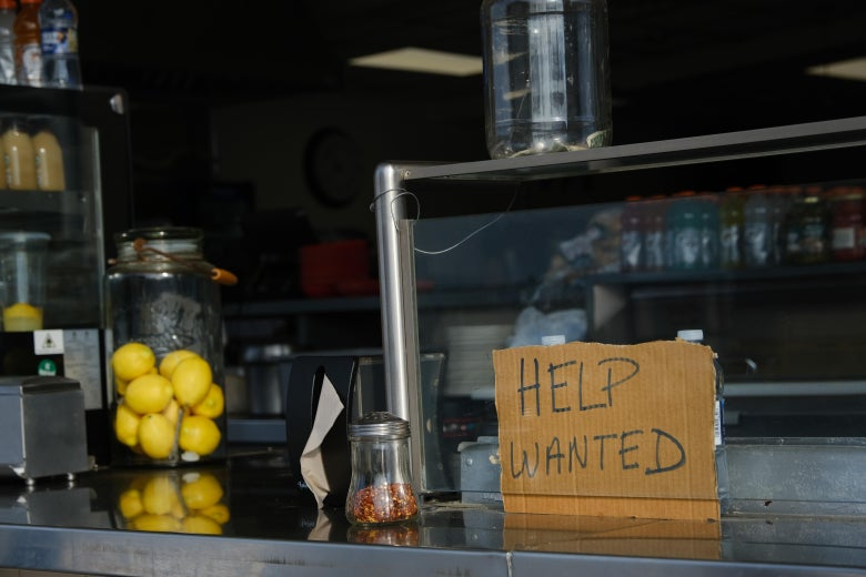 """A cardboard """"help wanted"""" sign on a counter inside a boardwalk restaurant in Wildwood, New Jersey"""