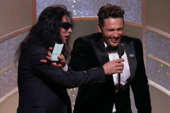 Tommy Wiseau, wearing sunglasses, reaches for the microphone while James Franco, laughing, blocks his arm