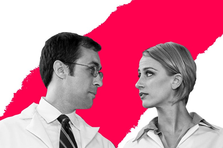 A man in a lab coat eyes a woman in a lab coat.
