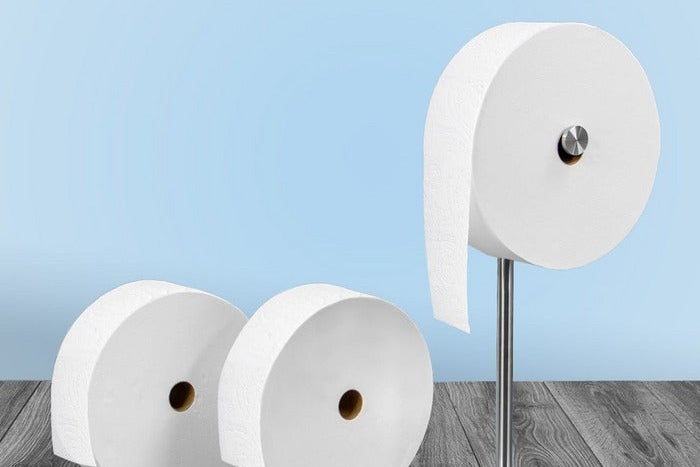A giant roll of toilet paper hangs on a stainless steel roll holder. Sitting next to it are two other giant rolls of toilet.