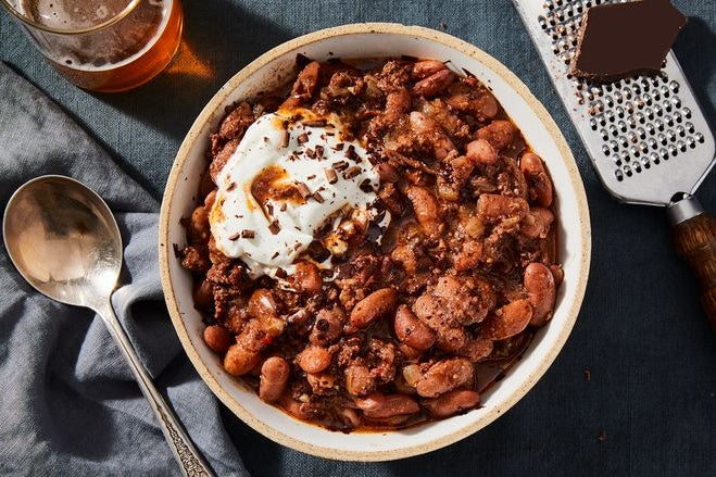A bowl of chili topped with a dollop of cream.