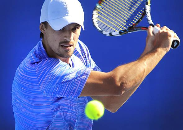 Denys Molchanov of Ukraine returns a shot against Malek Jaziri of Tunisia.