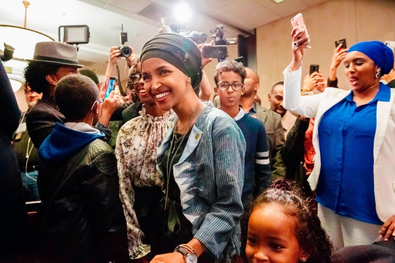 Ilhan Omar in a crowd of smiling supporters.