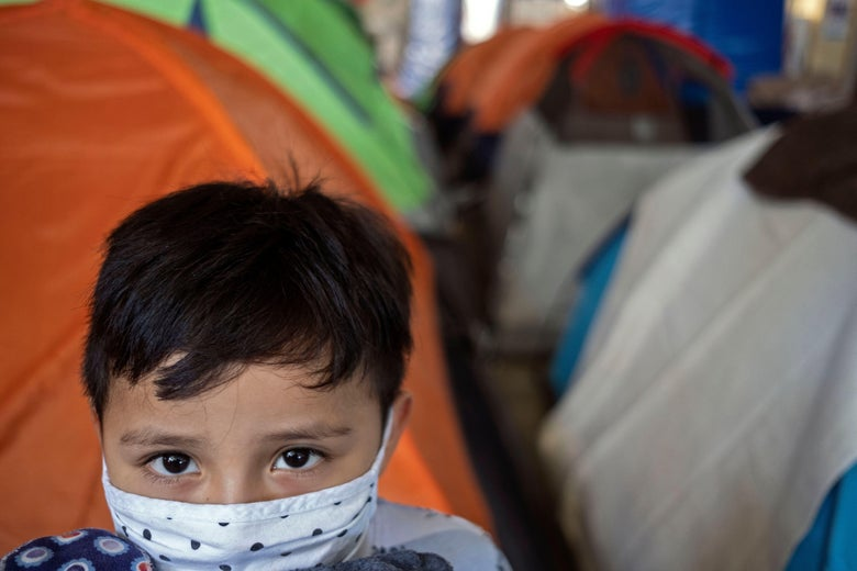 A boy wearing a face mask, with tents in the background