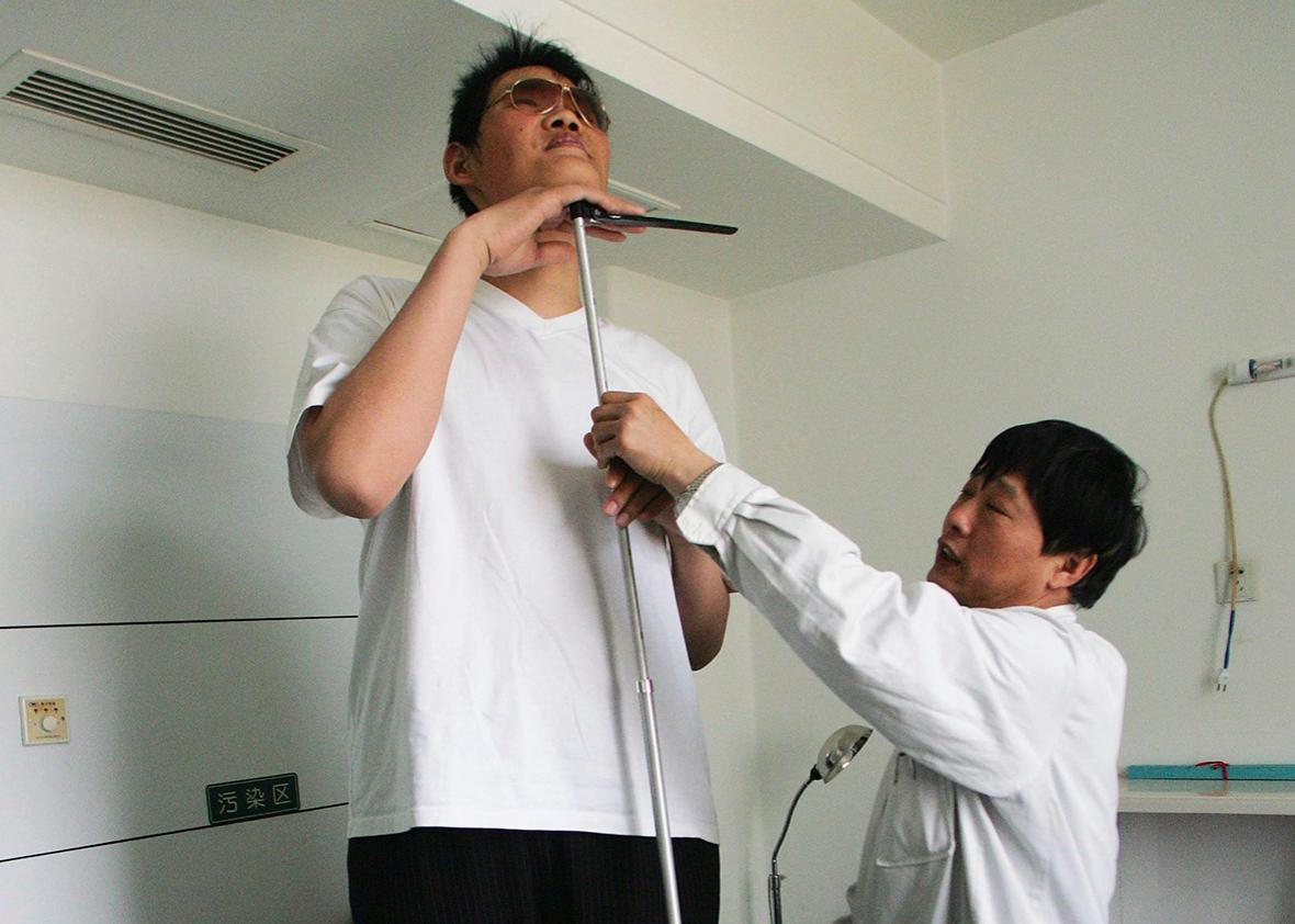 Zhao Liang, who may be the world's tallest person, has his height measured by a doctor before foot surgery at a hospital in Tianjin municipality April 13, 2009.