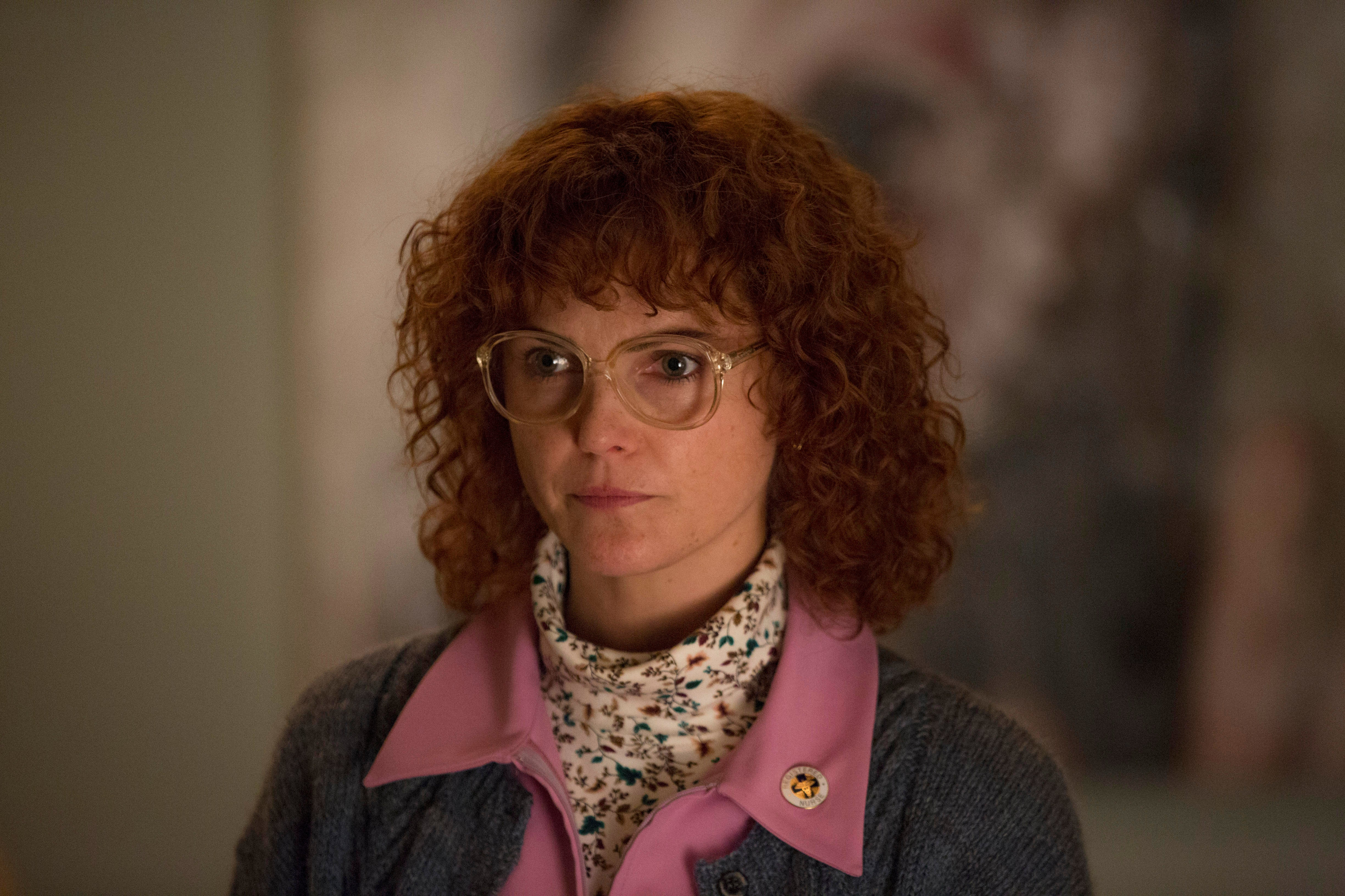 Keri Russell plays Elizabeth in The Americans. In this still, Elizabeth is in disguise as Stephanie, a dowdy home care nurse. She wears big, round glasses, a crazy-curly redhead wig, and a speckle-patterned white fluffy turtleneck under a pink-collared denim shirt.