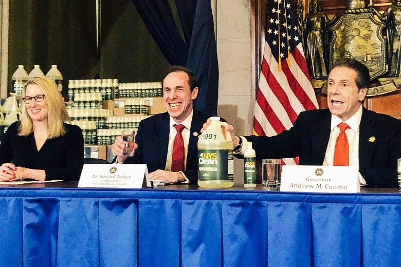 Cuomo, seated beside Dr. Howard Zucker on a panel, presents a jug of hand sanitizer at a briefing.