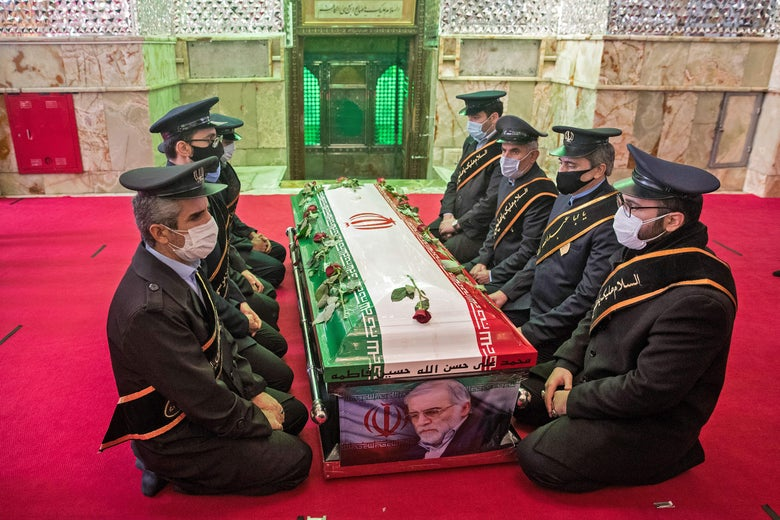 Uniformed soldiers kneel on the carpet around a coffin draped with an Iranian flag and a picture of Fakhrizadeh.