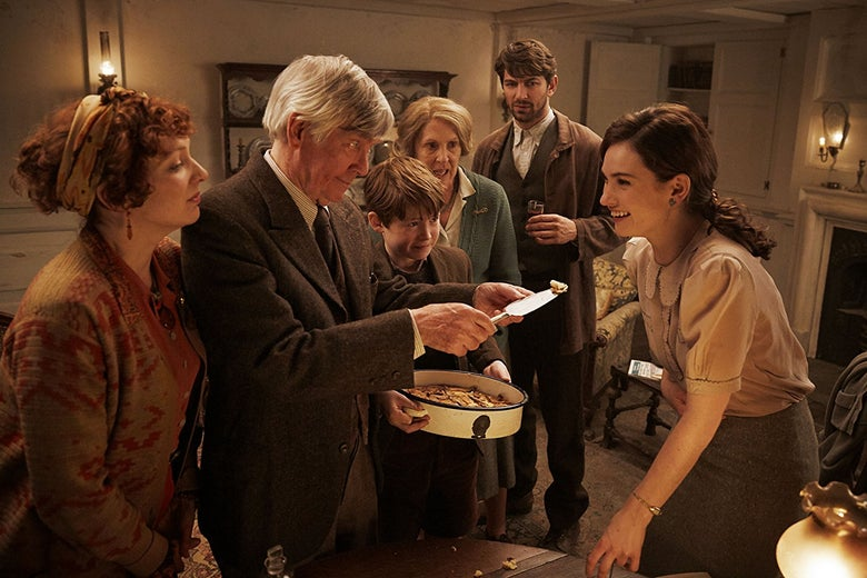 In a living room, Kit Connor holds a dish and Tom Courtenay offers Lily James a bite of food. They are standing in a living room with Michiel Huisman, Penelope Wilton, and Katherine Parkinson.