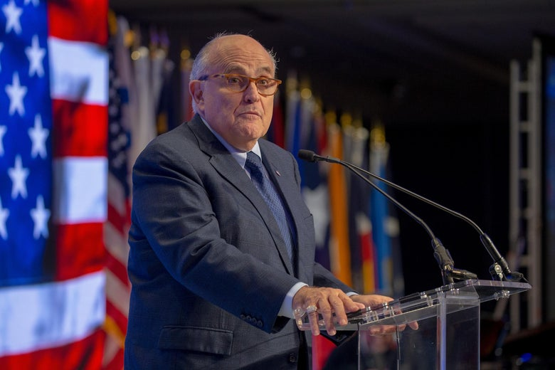 Rudy Giuliani stands at a glass podium.
