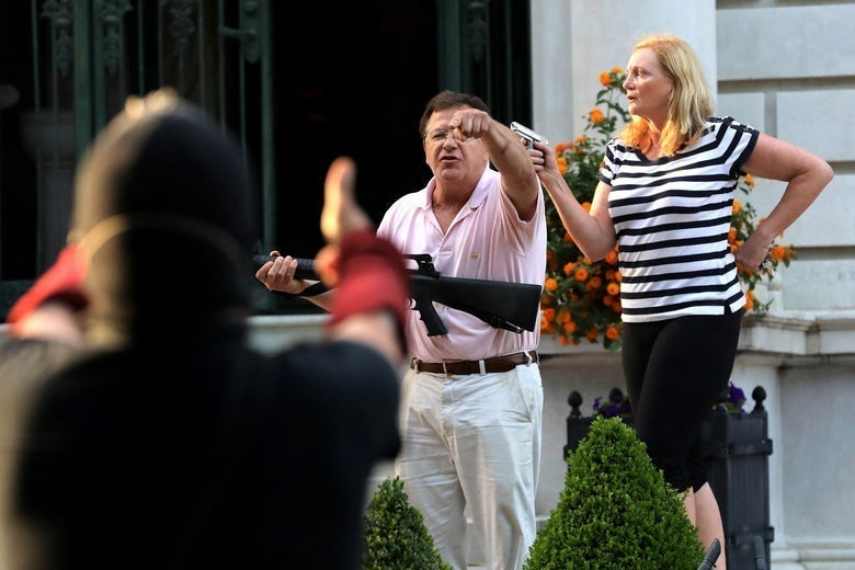 Mark, wearing a pink polo and khakis and holding a semi-automatic rifle, stands in front of his house and yells at a protester in the foreground. Patricia stands beside him, wearing a striped shirt and capris and pointing a handgun to her right.