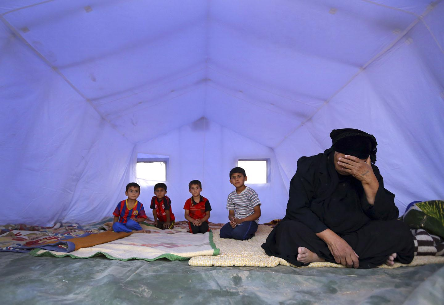 A family, who fled from the violence in Mosul, sits inside a tent at a camp on the outskirts of Erbil in Iraq's Kurdistan region, June 12, 2014.